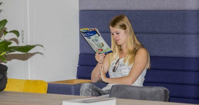 Client leest een boek in de wachtruimte