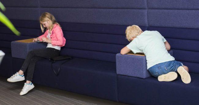 Wachtruimte van de Fijne Tandartsen met 2 spelende kinderen op de bank